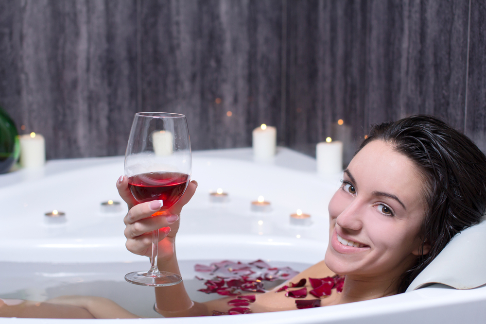 Girl drinking red wine while rest in tub